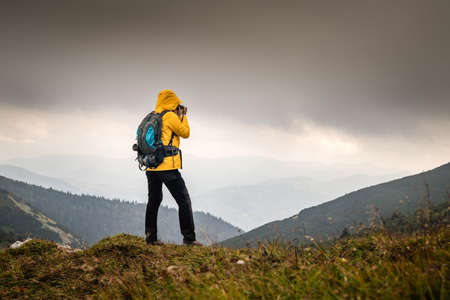Adventure in nature. Hiker photographing mountain range in bad weather. Woman with backpack hiking outdoors. Tourist taking photograph during hike