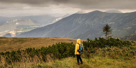 Hiker looking at mountain range know as Mala Fatra in Slovakia. Panoramic view to landscape. Woman tourist standing in nature. Adventure concept