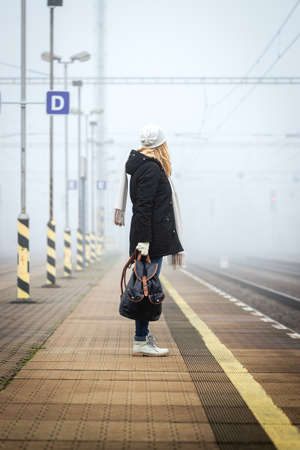 Woman with backpack waiting at railroad station for train. Foggy atmospheric mood in city. Tourist travel by train