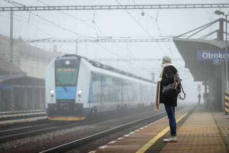 Woman traveler standing on railroad station platform and looking at arriving train from fog. Backpacker travel by train 版權商用圖片