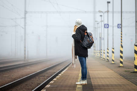 Woman waiting at railroad station for train. Foggy atmospheric mood in city. Tourist travel by train