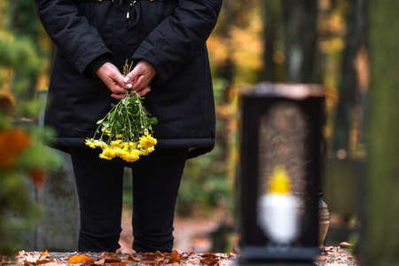 Mourning woman holding flowers in hands and standing at grave in cemetery. Sadness during funeral