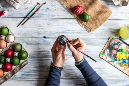 Painting Easter eggs. Woman making decoration for easter holiday. Table top view Stok Fotoğraf