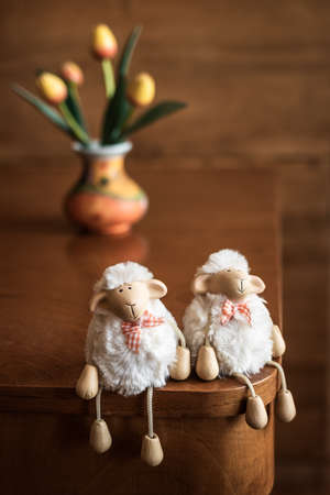 Funny sheep toys on wooden table, vase with tulips in background. Indoors decoration for Easter holidays
