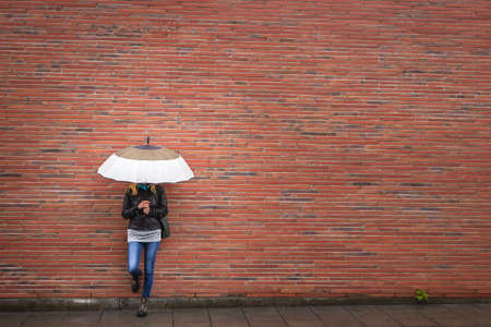 Woman with umbrella is leaning at red brick wall in city. Rain weather on the street. Fashionable woman wearing trendy clothes. Copy space Stok Fotoğraf