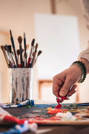 Artist mixing acrylic colors on a palette for painting.