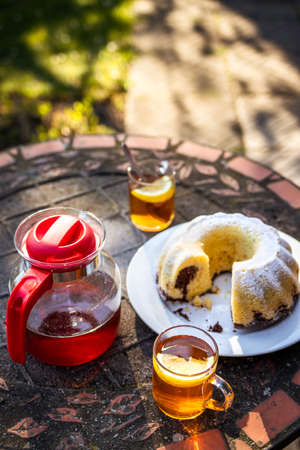 Tea in cup and teapot with bundt cake on table outdoors.