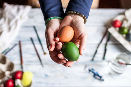 Woman holding colorful eggs in hands above table.