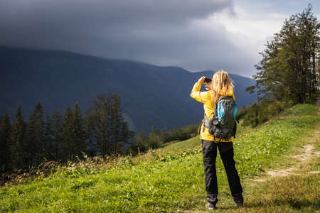 Storm is coming. Bad weather in mountains. Woman photographing on mobile phone during hike at mountain trail Stok Fotoğraf