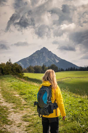 Mountains trekking. Woman hiking on trail in natural park Mala Fatra, Slovakia. Majestic mountain peak known as Velky Rozsutec in background with dramatic sky