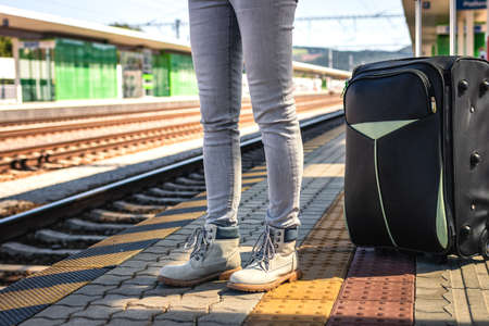 Woman with suitcase waiting at railroad station platform. Travel to vacation with large luggage by train Stok Fotoğraf