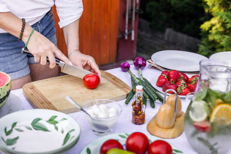 Preparing mediterranean dish for garden party. Woman is chopping red tomato on cutting board for vegetable salad