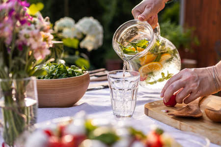 Pouring water with mint herbs and lemon from pitcher into drinking glass. Woman preparing healthy food and drinks