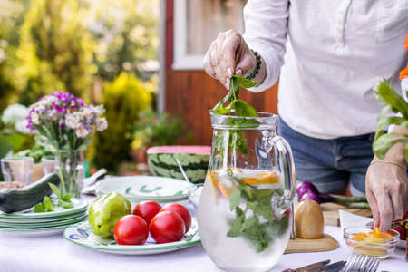 Woman putting mint herb into cold lemonade in pitcher. Preparing non-alcoholic drink for garden party Stok Fotoğraf