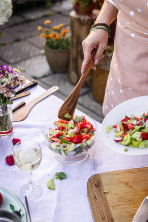 Woman serving fresh vegetable salad outdoors. Healthy vegetarian food on banquet and garden party