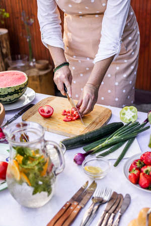 Preparing vegetable salad outdoors. Woman chopping red tomato on cutting board. Cooking with fresh ingredient Stok Fotoğraf