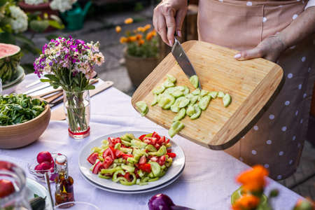 Preparation vegetable salad from cucumber, pepper and tomatoes. Woman cooking healthy vegetarian food outdoors Stok Fotoğraf