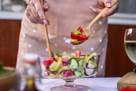 Woman mixing chooped vegetable in glass salad bowl. Preparing and cooking healthy vegetarian food