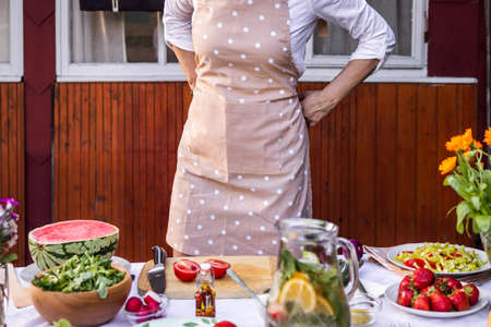 Woman tying apron and getting ready for cooking. Making fresh healthy food for garden party outdoors Stok Fotoğraf