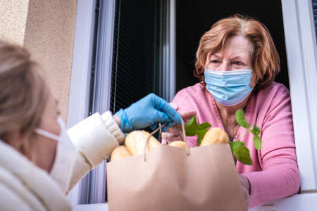 Woman delivering groceries and food to her senior mother. Social distancing due coronavirus pandemic lockdown Stok Fotoğraf