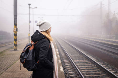 Woman waiting for train at railway station in foggy morning. Female tourist with backpack traveling alone