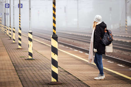 Female tourist with backpack waiting for train at empty railroad station platform. Woman travel by train