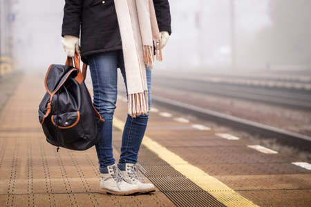 Traveler with backpack standing at railroad station and waiting for train. Woman tourist wearing jeans and boots