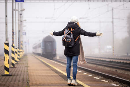 Disappointed traveler missed train. Woman tourist is looking at leaving train on railroad station