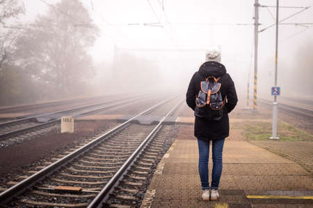 Woman traveler waiting for train at railway station in foggy morning. Female tourist with backpack traveling alone