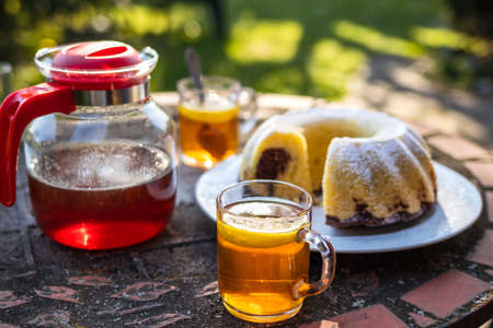 Tea in cup and teapot with bundt cake on table outdoors. Serving dessert and hot drink in spring garden. Picnic at springtime