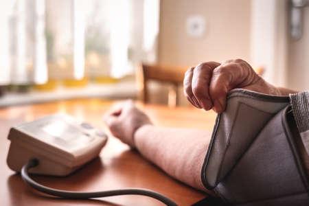 Blood pressure gauge medical device. Senior woman is checking her hypertension. Diagnostic medical tool