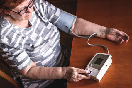 Senior woman measuring blood pressure at home. Everyday life for hypertension patient