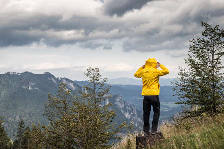 Strong wind in the mountains. Woman wearing sports clothing during hiking in wilderness. The weather in the mountains is changing rapidly