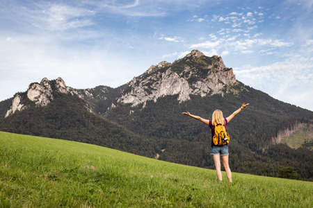 Happy woman enjoying hiking in mountains. Travel and active lifestyle concept. Carefree female tourist is feeling fresh air in nature Stock fotó
