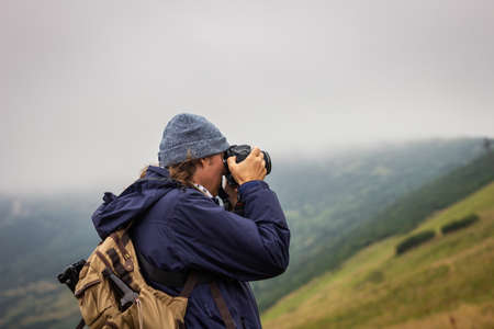 Hiker with camera is taking picture of landscape during hiking at mountains. Adventure in nature