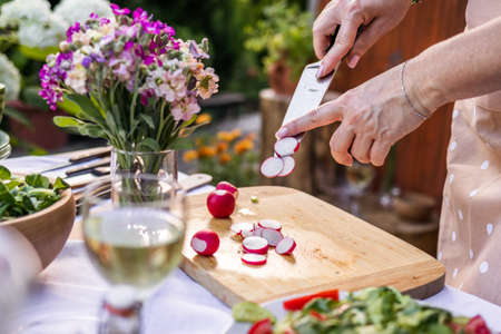 Woman chopping radish with kitchen knife on cutting board. Cooking and preparing food and vegetable salad Stock fotó