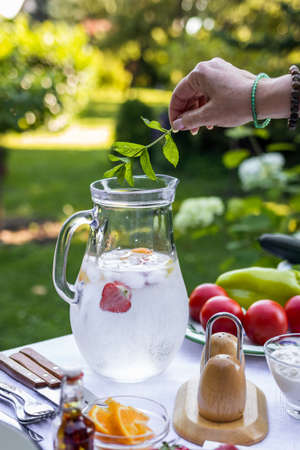 Female hand putting mint herb into cold lemonade in pitcher. Preparing non-alcoholic drink for garden party