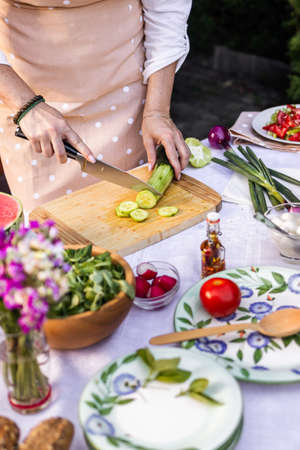Woman with apron cutting cucumber for vegetable salad. Female chef is cooking healthy mediterranean food outdoors Stock fotó