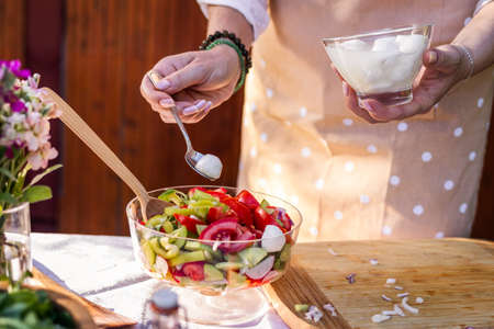 Vegetable salad with mozzarella cheese. Woman preparing mediterranean food on table outdoors Stock fotó