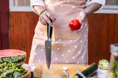 Woman wearing apron and holding kitchen knife and red tomato. Cooking vegetable salad