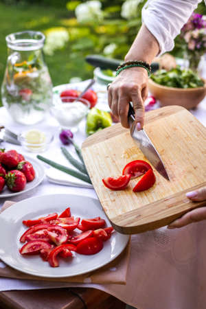 Chopped tomatoes on cutting board. Woman cooking fresh vegetable salad in garden Stock fotó