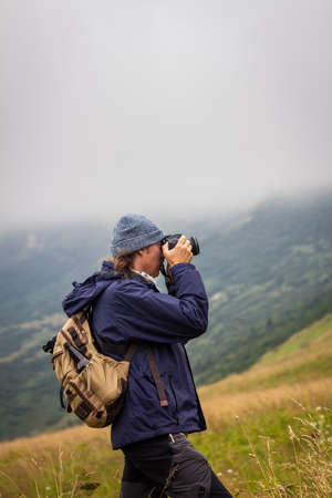 Traveler with camera is taking picture of landscape during hiking at mountains. Adventure in nature Stock fotó