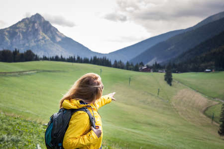 Woman pointing at mountain trail during hike. Female tourist trekking during vacation in mountains know as Mala fatra, Slovakia