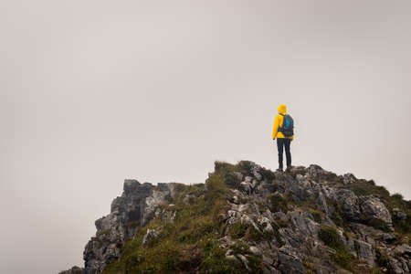 Hiker with backpack standing on the top of mountain peak. Climbing and hiking in bad weather