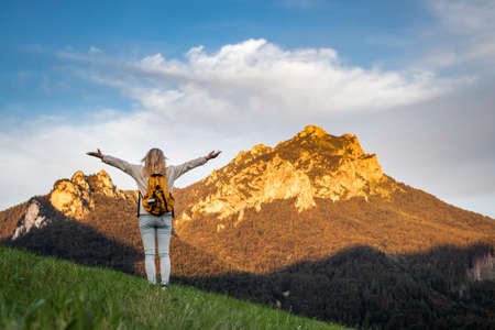 Woman enjoying hiking in mountains. Travel and active lifestyle concept. Carefree female tourist is feeling fresh air in nature