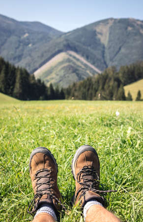 Leather hiking boots. Point of view tourist resting during hike in mountains. Sport outdoor shoes