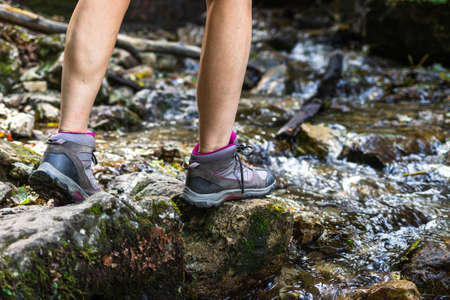 Woman with hiking boots walking on rocks in river. Tourist trekking at mountain trail