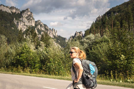 Traveler hiking on road at mountains in natural park Mala Fatra, Slovakia. Travel and active lifestyle concept. Woman with backpack during summer vacation
