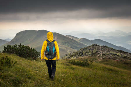 Tourist hiking at mountains in bad weather. Trekking in natural parkland Mala fatra, Slovakia