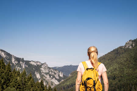 Female tourist looking at rocky mountains. Woman with backpack hiking in nature during summer vacation. Clear blue sky as copy space Stock fotó